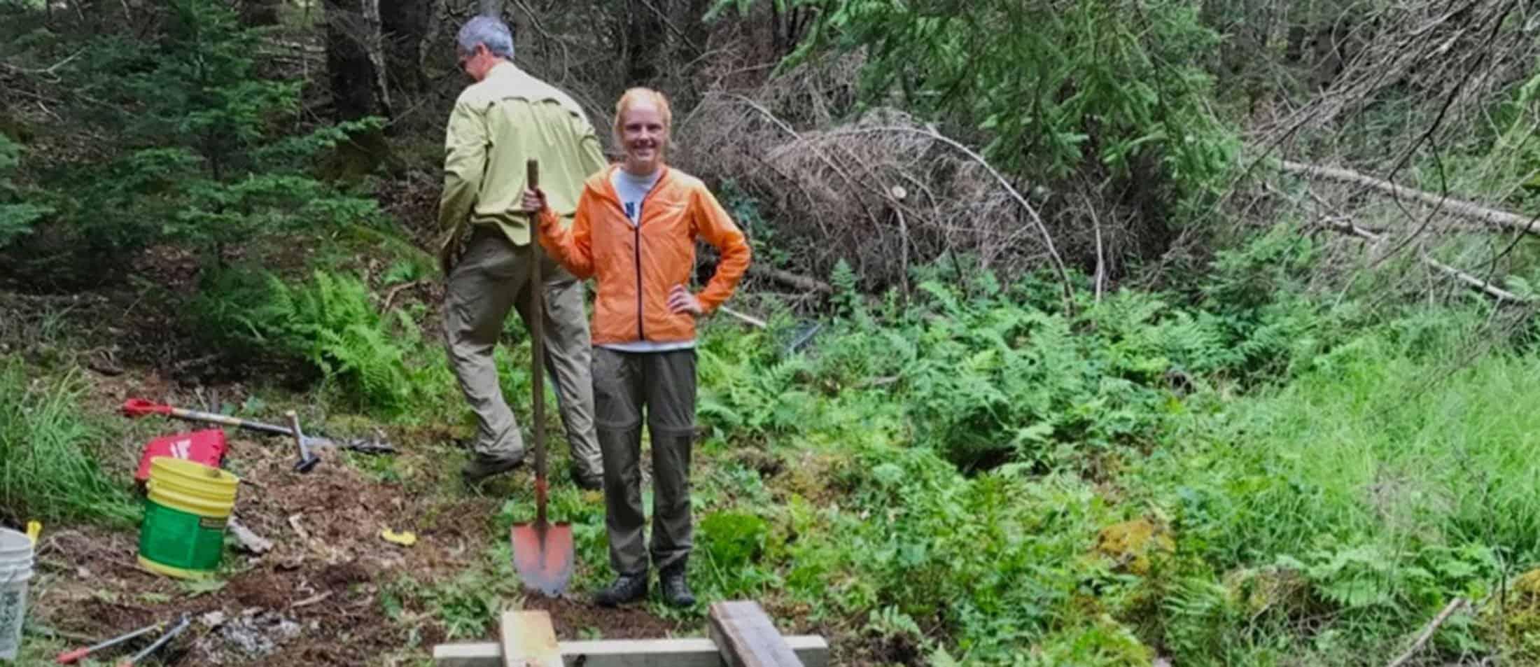 Blue Hill Heritage Trust's Intern helping to build a bridge on John B Mountain's new trail.
